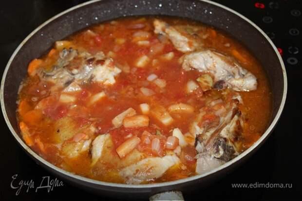 Добавляем томатно-овощную смесь к курице. Доливаем воды так, чтобы она слегка покрывала содержимое сковороды. Доводим до кипения и тушим на небольшом огне под закрытой крышкой около 15 минут. Затем снимаем крышку и тушим еще 15 минут, до полной готовности курицы и моркови.